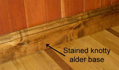 Stained knotty alder base moulding made at Buckeye Hardwood & Lumber Co. Also shown, cherry beveled edge paneling and white oak floor with walnut feature strip.