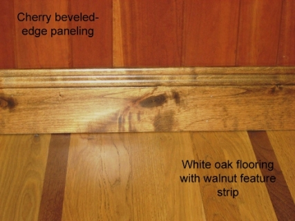 WP-4 cherry paneling, knotty alder base moulding, and white oak flooring with walnut feature strip in Arlee showroom